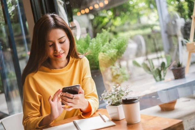 woman smiling while scrolling on a smartphone