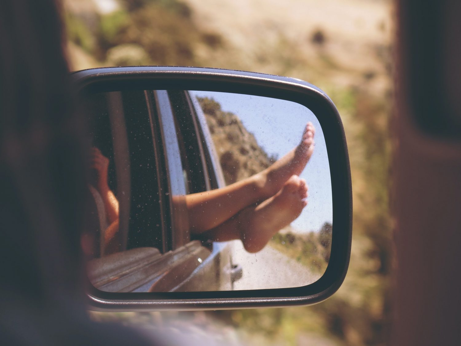 woman's feet in rear view mirror