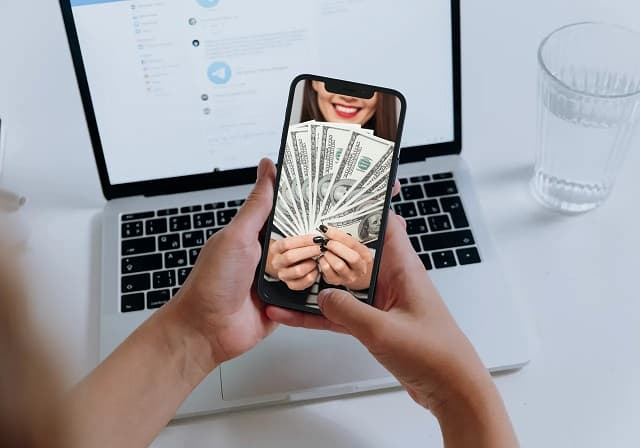 person looking at smartphone image of woman holding money