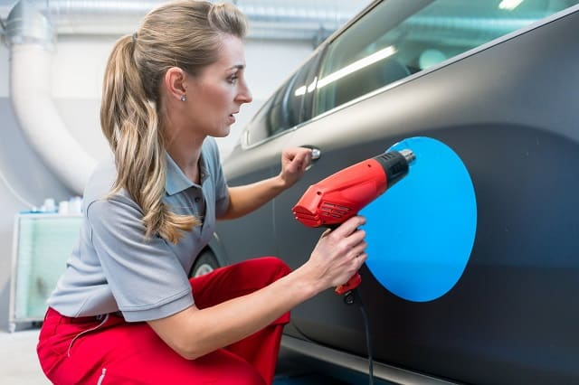 Woman with legitimate car wrap advertising company installing decal