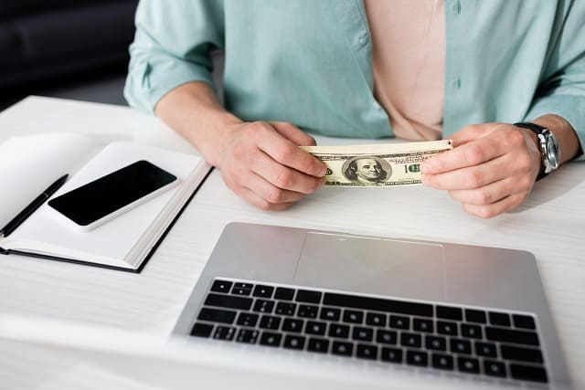 woman holding cash that she earned online instantly for free