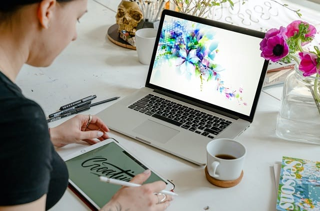 woman designing graphics on a laptop