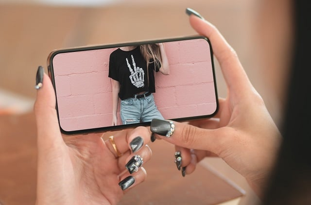 Woman taking picture of t-shirt to list on Poshmark