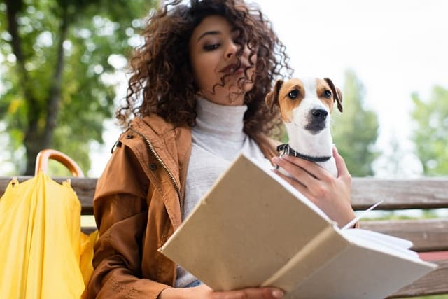Woman reading next to a dog
